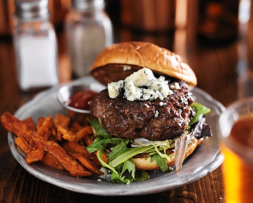 gourmet hamburger with blue cheese, sweet potato fries and beer